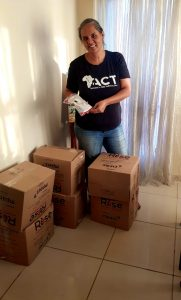 Hilary Leong standing in front of food parcel boxes to be delivered to families during COVID-19-2